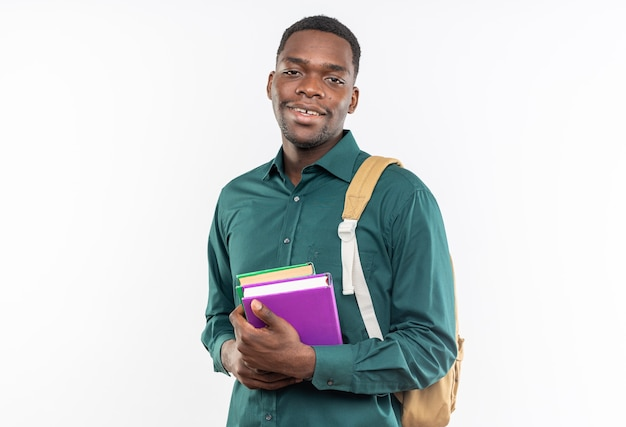 Sorridente giovane studente afro-americano con lo zaino in possesso di libri