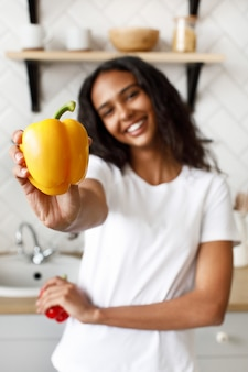 Smiling young afro girl shows close up a yellow pepper