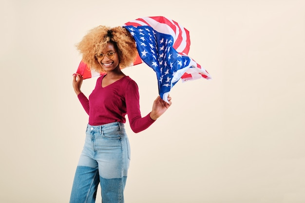 Smiling young afro woman waving a us flag while standing on an isolated background. usa independence day and patriotism concept.