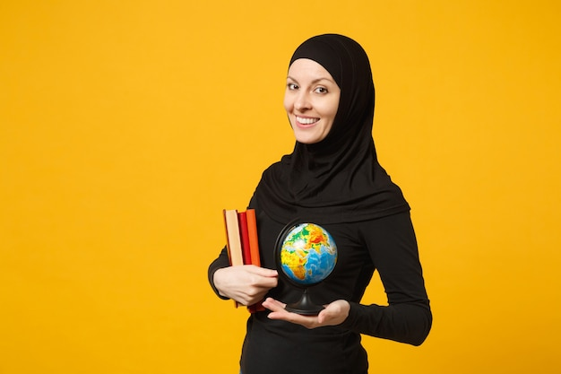 Smiling young arabian muslim student girl in hijab black clothes hold in hands globe, books isolated on yellow wall  portrait. people religious lifestyle concept.