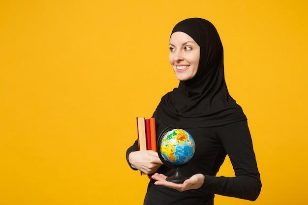 ヒジャーブの黒い服を着た若いアラビアのイスラム教徒の学生の女の子の笑顔は、地球儀、黄色の壁の肖像画で隔離された本を手に持っています。人々の宗教的なライフスタイルの概念。