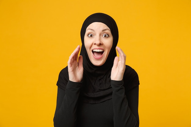 Smiling young arabian muslim woman in hijab black clothes whispering secret behind her hand isolated on yellow wall, portrait. people religious lifestyle concept.