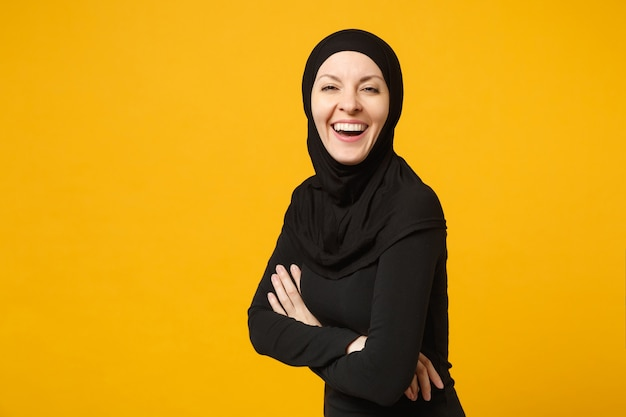 ヒジャーブの黒い服を着て笑顔の若いアラビアのイスラム教徒の女性は、黄色の壁、肖像画で隔離、手を組んで保持します。人々の宗教的なライフスタイルの概念。