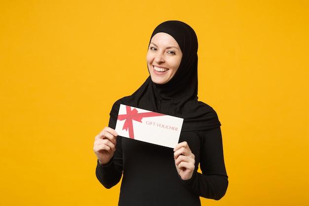 ヒジャーブの黒い服を着て笑顔の若いアラビアのイスラム教徒の女性は、黄色の壁の肖像画に分離されたギフト券を手に持っています。人々の宗教的なライフスタイルの概念。