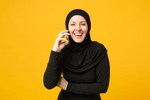 ヒジャーブの黒い服を着て笑顔の若いアラビアのイスラム教徒の女性は、黄色の肖像画に分離された携帯電話で話している手を握ります。人々の宗教的なライフスタイルの概念。 。