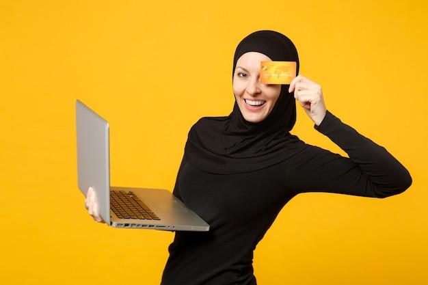 ヒジャーブの黒い服を着た若いアラビアのイスラム教徒の女性の笑顔は、ラップトップpc、黄色の壁の肖像画に分離されたクレジット銀行カードを保持します。人々の宗教的なライフスタイルの概念。