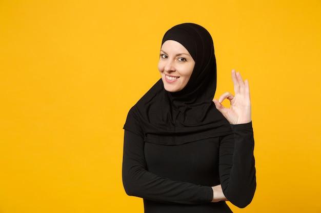 黄色の壁、肖像画に分離されたokジェスチャーを示すヒジャーブの黒い服を着た若いアラビアのイスラム教徒の女性の笑顔。人々の宗教的なライフスタイルの概念。