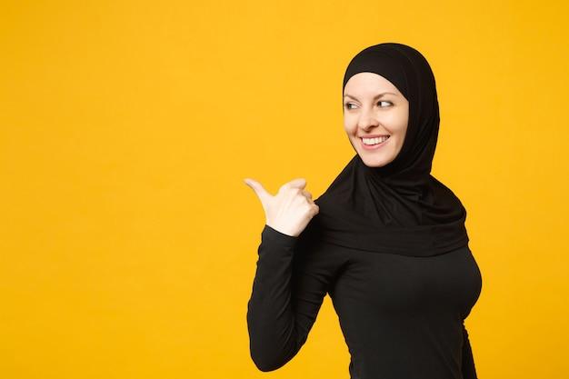 黄色の壁の肖像画に分離された手指でポインティングコピースペースを示すヒジャーブの黒い服を着た若いアラビアのイスラム教徒の女性の笑顔。人々の宗教的なライフスタイルの概念。