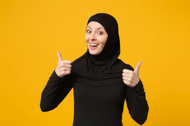 黄色の壁、肖像画で隔離、親指を上に表示しているヒジャーブの黒い服を着て笑顔の若いアラビアのイスラム教徒の女性。人々の宗教的なライフスタイルの概念。