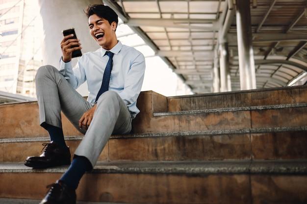 市内で携帯電話を使用して笑顔の若いasainビジネスマン。階段に座る