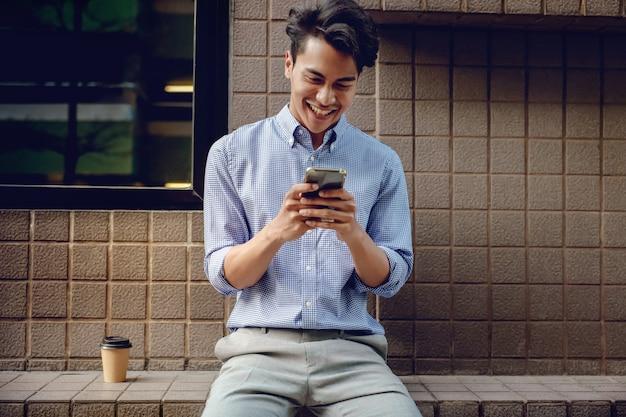 街で携帯電話を使用して笑顔の若いasainビジネスマン