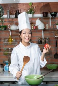 Улыбающийся шеф-повар молодой азиатской женщины в белой форме, стоя на кухне, показывая красное яблоко на руке.