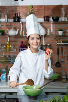 Smiling young asia woman chef cook in white uniform standing at the kitchen, showing red apple on her hand.