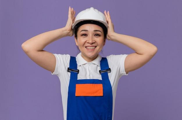 Sorridente giovane ragazza asiatica del costruttore che mette le mani sul suo casco di sicurezza bianco