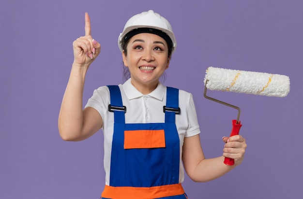 Smiling young asian builder girl with white safety helmet holding paint roller and pointing up