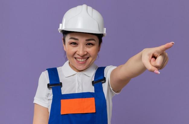 Улыбающаяся молодая азиатская девушка-строитель с белым защитным шлемом, смотрящая вперед и указывающая в сторону