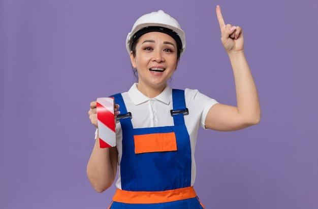 흰색 안전 헬멧을 쓰고 경고 테이프를 들고 위를 가리키는 웃고 있는 젊은 아시아 건축업자 여성