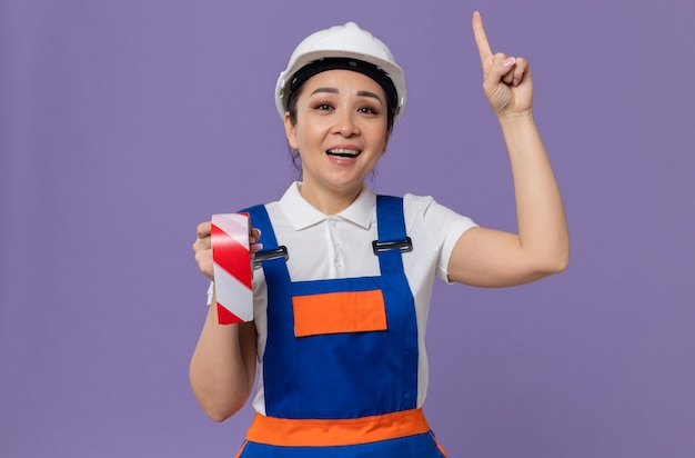 Sorridente giovane donna asiatica costruttore con casco di sicurezza bianco che tiene il nastro di avvertimento e rivolto verso l'alto