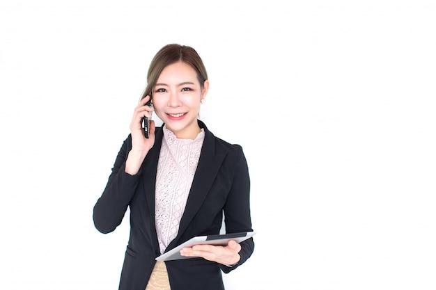 Усмехаясь молодая азиатская бизнес-леди с технологией таблетки и умный телефон изолированные на белой стене с космосом экземпляра