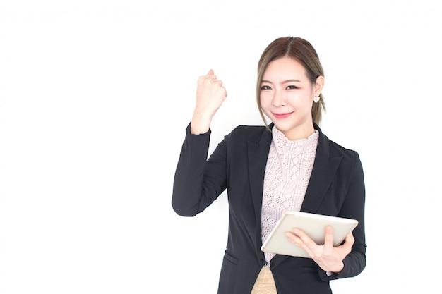Усмехаясь молодая азиатская бизнес-леди с технологией таблетки изолированная на белой стене с космосом экземпляра