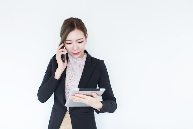 Smiling young asian business woman with tablet technology and smart phone with copy space