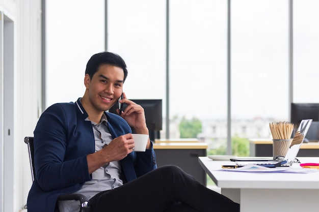 Smiling  young asian businessman talking on his mobile phone and drinking coffee in office with laptop computer.