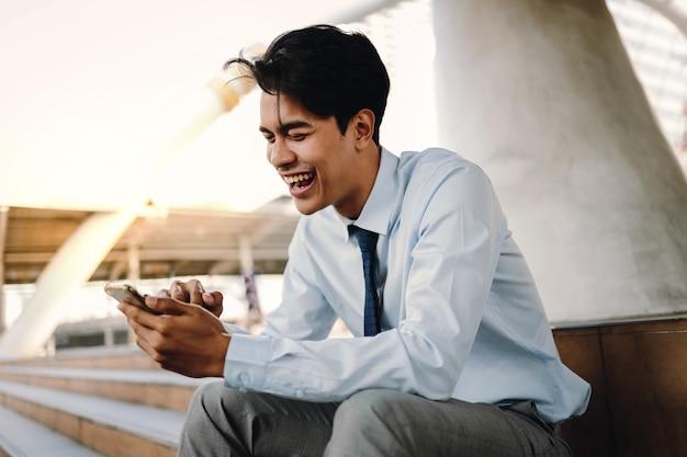 市内で携帯電話を使用して笑顔の若いアジア系のビジネスマン。階段に座る