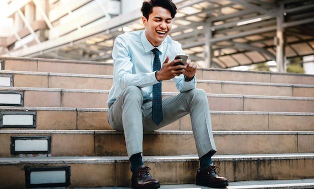 市内で携帯電話を使用して笑顔の若いアジア人ビジネスマン。階段に座って