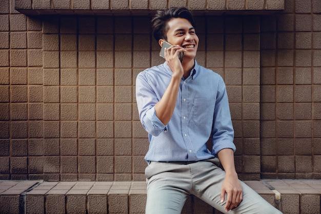 市内で携帯電話を使用して笑顔の若いアジア人ビジネスマン