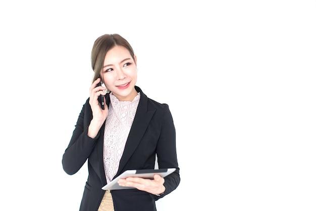 태블릿 기술을 들고 스마트폰으로 말하는 웃고 있는 젊은 아시아 여성