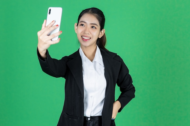 Smiling young asian businesswoman taking picture of herself