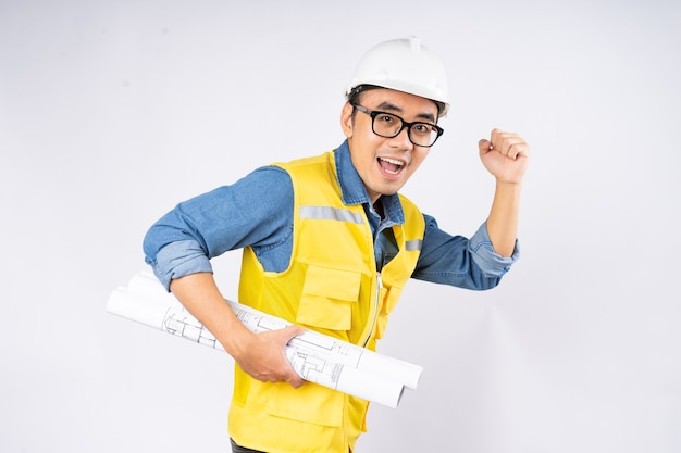 Усмехаясь молодой азиатский инженер-строитель в каске каски стоя на изолированной белой предпосылке. концепция обслуживания механика.