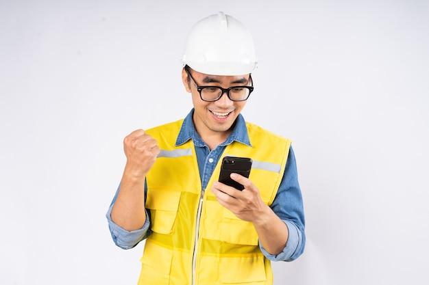 孤立した白い背景の上に立っているヘルメットハード帽子をかぶって笑顔の若いアジアの土木技師。メカニックサービスのコンセプト。