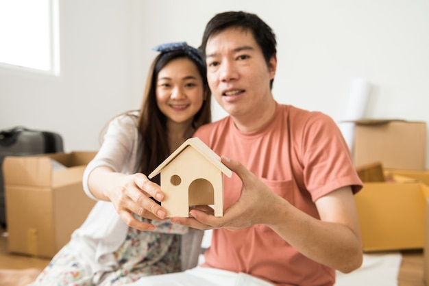Улыбающаяся молодая азиатская пара держит макет деревянной модели дома в своем новом доме с множеством движущихся картонных коробок и багажа в пустой главной спальне