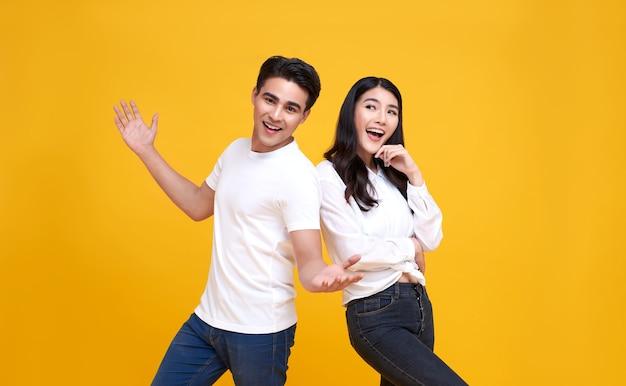 Улыбающиеся молодые азиатские пара мужчина и женщина счастливы и изумлены на желтом.