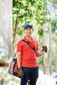 카페의 밝은 유니폼 여는 문에 웃는 젊은 아시아 배달 남자