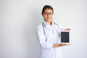 Smiling young Asian female doctor showing tablet computer screen.