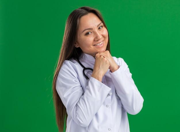 의료 가운과 청진기를 입고 웃고 있는 젊은 아시아 여성 의사가 복사 공간이 있는 녹색 벽에 격리된 정면을 바라보며 턱 아래에서 손을 모으고 있습니다.