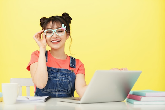Smiling young asian female student in brightly colored glasses sitting at desk with laptop