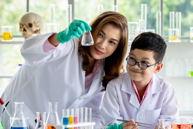 Smiling young asian female teacher and smart schoolboy in white lab coats examining fluid in flask during chemical research in modern scientific laboratory.
