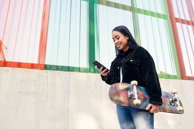 야외에서 스케이트보드를 손에 들고 휴대전화에 타이핑을 하는 웃고 있는 아시아 소녀