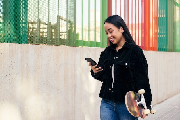 그녀의 손에 스케이트보드를 들고 거리를 걷는 동안 휴대 전화에 입력 웃는 젊은 아시아 여자