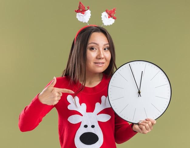 올리브 녹색 배경에 고립 벽 시계에 크리스마스 머리 후프 지주와 포인트를 입고 웃는 젊은 아시아 소녀