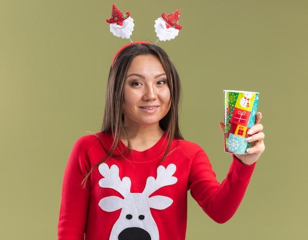 Giovane ragazza asiatica sorridente che porta il cerchio dei capelli di natale che tiene fuori la tazza di natale alla macchina fotografica isolata su fondo verde oliva