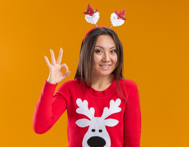 Улыбающаяся молодая азиатская девушка в рождественском обруче для волос со свитером, показывающим нормальный жест, изолирована на оранжевой стене