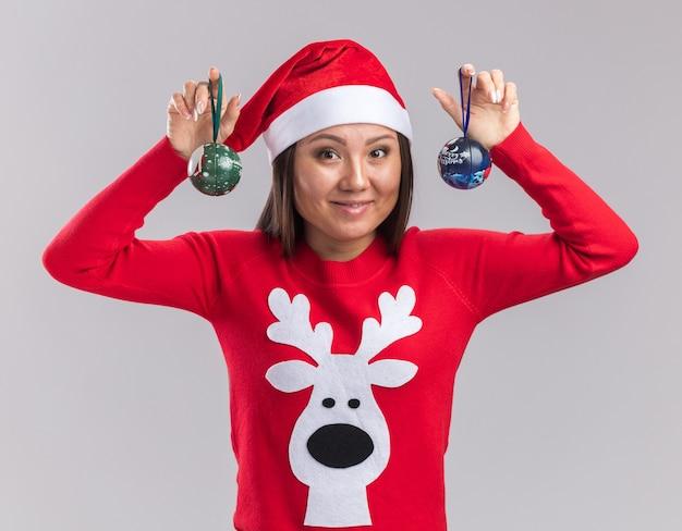 흰색 배경에 고립 된 크리스마스 트리 볼을 들고 스웨터와 크리스마스 모자를 쓰고 웃는 젊은 아시아 소녀