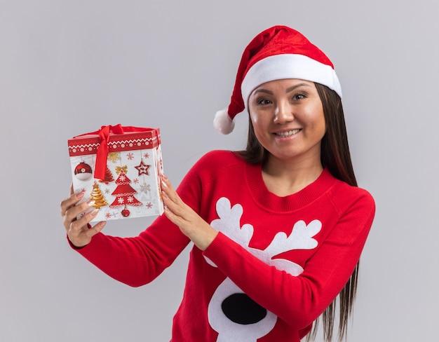 Улыбающаяся молодая азиатская девушка в новогодней шапке со свитером держит подарочную коробку на белом фоне