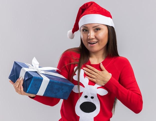 白い背景で隔離の自分に手を置くギフトボックスを保持しているセーターとクリスマス帽子をかぶって笑顔の若いアジアの女の子