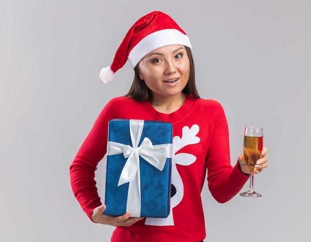 Улыбающаяся молодая азиатская девушка в новогодней шапке со свитером, держащая подарочную коробку с бокалом шампанского, изолированную на белом фоне