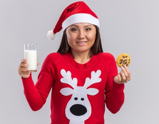 Sorridente giovane ragazza asiatica che indossa il cappello di natale con maglione tenendo un bicchiere di latte e biscotti isolati su sfondo bianco